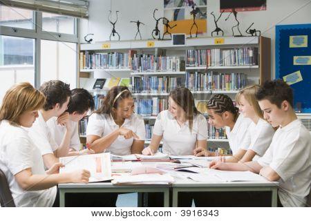 Adolescentes alunos estudando na biblioteca da escola