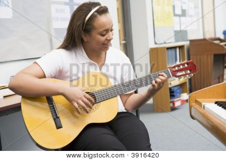 Teen Pupil Learning The Guitar In Classroom