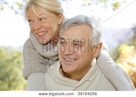 Senior man giving piggyback ride to wife