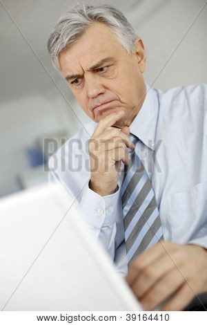 Senior man with puzzled look in front of laptop