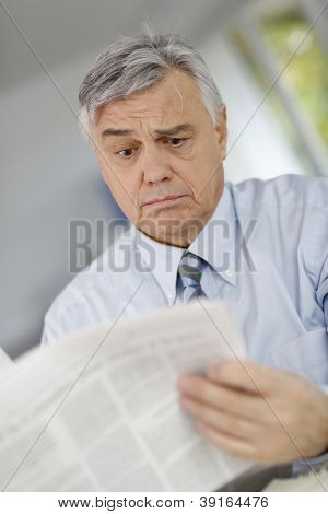 Senior businessman reading news with inquiring look