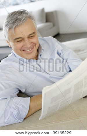 Senior man smiling as reading the newspaper