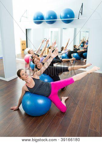 Grupo de mulheres aeróbio do Pilates com bola de estabilidade em uma linha no ginásio espelho