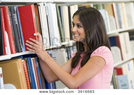 Woman In Library Pulling Book Off A Shelf (Depth Of Field)