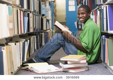 Man Sitting On Floor In Library Holding Book