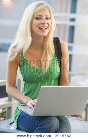 Woman Sitting On Bench Outdoors With Laptop Smiling (Selective Focus)