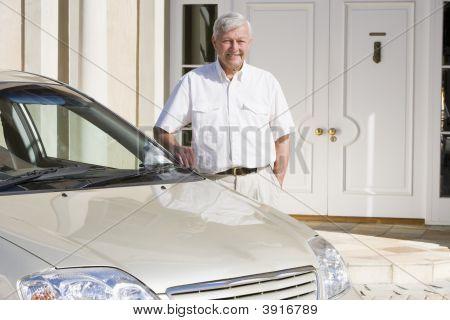 Senior Mann mit seinem Auto außerhalb seiner Heimat