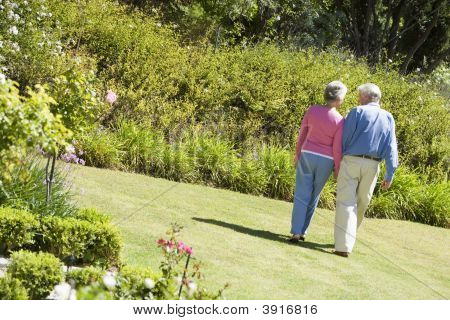 Senior Couple Walking Through A Flower Garden