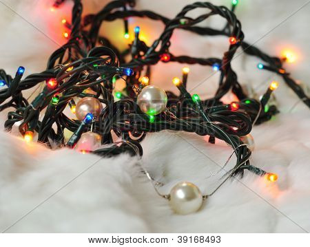 Christmas Garland Lit With Colored Lights On White Fur With Pearls