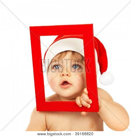 Picture of cute infant looking through red Christmas frame isolated on white background, little boy dressed in pretty Santa Claus hat, winter holidays, xmas celebration, New Year eve, happy childhood