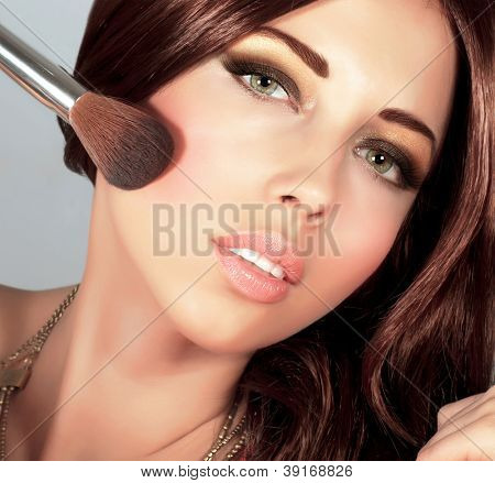 Photo of beautiful stylish woman doing makeup, closeup portrait of pretty female with silky brown hair holding brush for blush isolated on grey background, smoky eyes, fashionable makeover