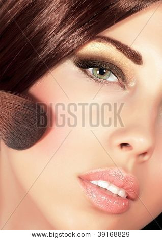 Picture of gorgeous woman with brown silky hair doing evening makeover, sexy look, smoky eyes, fashionable makeup, stylish visage, professional cosmetics brush and tassel, luxury beauty salon