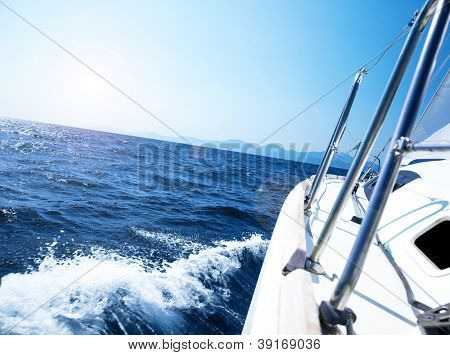 Photo of a 43 foot sailboat in action, speeding at open blue sea, parts of a luxury yacht boat, extreme water sport adventure, freedom and active lifestyle concept