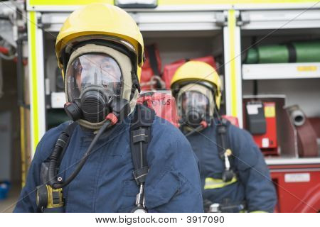 Two Firemen In Masks Standing Near Fire Engine (Depth Of Field)