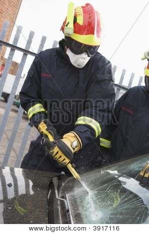Two Firefighters Cutting Out A Windshield After An Accident