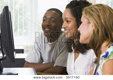 Three Students Sitting At A Computer Terminal (High Key)