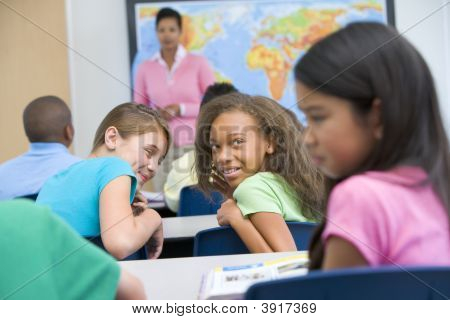 Students In Class Bullying Student With Teacher In Background (Selective Focus)