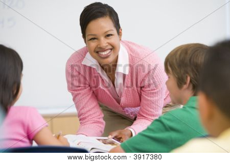 Teacher Helping Student In Class (Selective Focus)