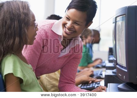 Teacher Helping A Student At Computer Terminal With Students In Background (Selective Focus/High Key