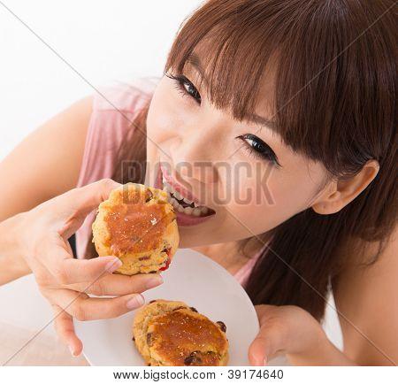 Young Asian woman enjoying scones