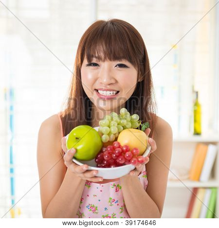Asian woman holding a bowl fresh fruit