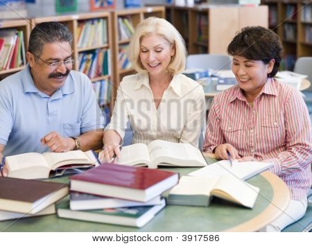Three People Sitting In Library With Books And Notepads (Selective Focus)
