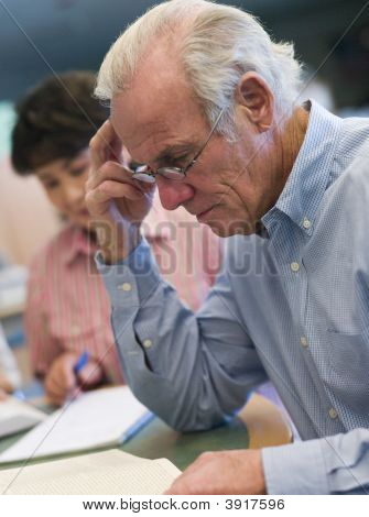 Man Sitting Near Woman In Library With Books And Notepads (Selective Focus)