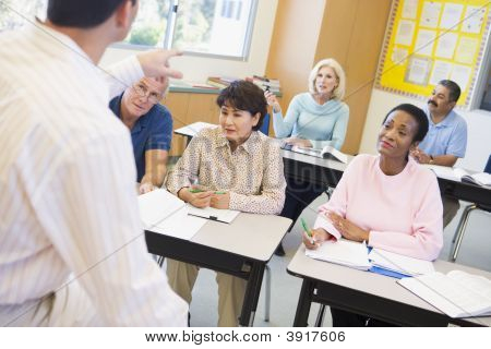 Adult Students In Class With Teacher (Selective Focus)