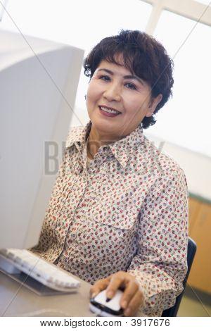 Mujer en computadora sonriendo y mirando el Monitor (alta llave)