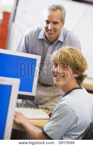 Teacher With Male Student In Computer Class