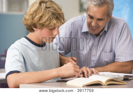 Teacher Giving Personal Instruction To Male Student