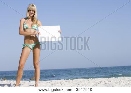 Woman Holding A Blank Card On A Beach