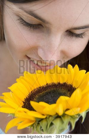 Woman Holding And Smelling A Sunflower