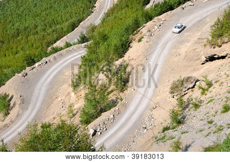 a old mercedes is traveling downhill on the winding dirt road into the Valley of the Kelmend between the albanian mountains