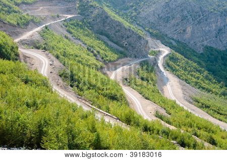 a winding dirt road go down into the Valley of the Kelmend between the albanian mountains
