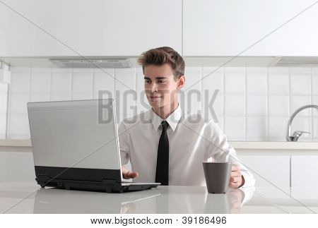 Young man in tie using a laptop computer during the breakfast, in a white kitchen