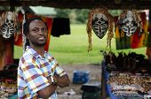 African Curio Salesman In Front Of Ethnic Masks