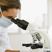pic of crime solving  - Female Doctor with mask on in lab with Microscope - JPG