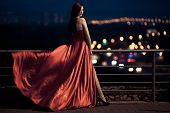 stock photo of flutter  - Young Beauty Famous Woman In Fluttering Red Dress Outdoor - JPG