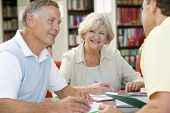 image of senior-citizen  - Three people in library writing in notebooks  - JPG