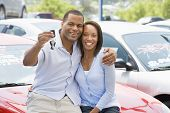 Couple Sat On Car With Keys