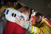 stock photo of crew cut  - Two firemen helping woman with neck brace - JPG