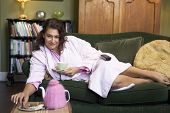 pic of housecoat  - Young woman lying on sofa at home eating cookies and drinking tea - JPG