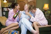 image of housecoat  - Three woman in night clothes sitting at home drinking wine - JPG