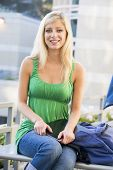 Woman Sitting On Bench Outdoors With Notebook Smiling (Selective Focus)