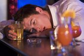 stock photo of alcohol abuse  - Drunk young man passed out in bar - JPG