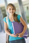 image of tweeny  - Student standing outside school with binder smiling  - JPG