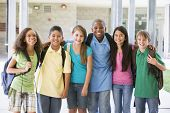 stock photo of knapsack  - Six students standing outside school together smiling - JPG