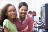 stock photo of tweeny  - Teacher and student at computer terminal with students in background  - JPG