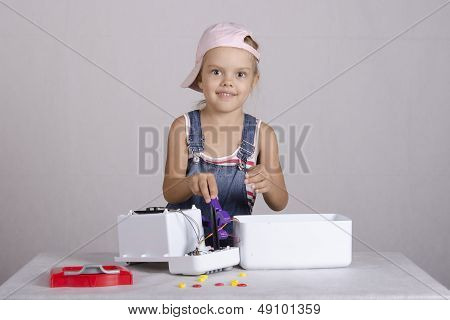 Girl repairs toy microwave